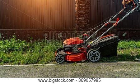 Lawnmower Mows The Grass Against The Fence