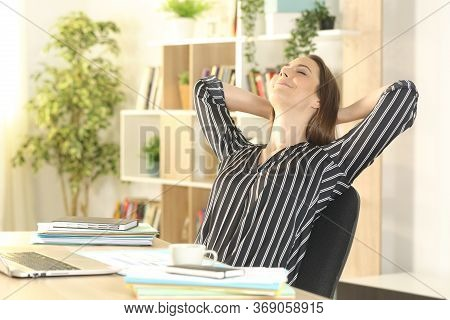 Satisfied Entrepreneur Woman Relaxing Sitting On A Desk At Homeoffice