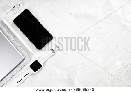 Flat Lay Of Modern Electronic Devices: Smartphone, Smartwatch, Digital Tablet, Stylus Pencil And Wir