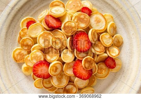 Trendy Food - Pancake Cereal. Heap Of Mini Cereal Pancakes With Strawberries On A Plate. Close Up. T