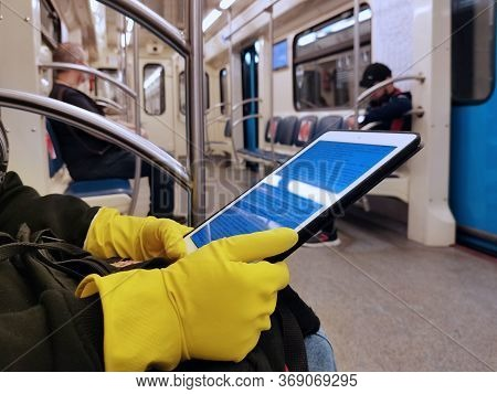 May 2020, Moscow, Metro. Hands In Yellow Gloves Hold The Ipad. Reading In The Subway. Precautions Ag