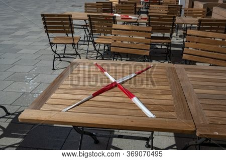Locked Table With Red And White Flutter Band In A Street Cafe During The Coronavirus Crisis, Keeping