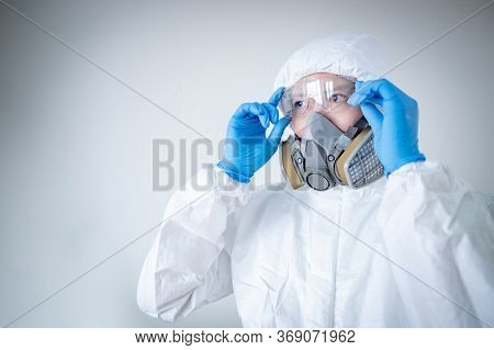 Scientist Or Virologist Man Wearing Biohazard Chemical Protective Suit, Goggles And Mask. Male Docto