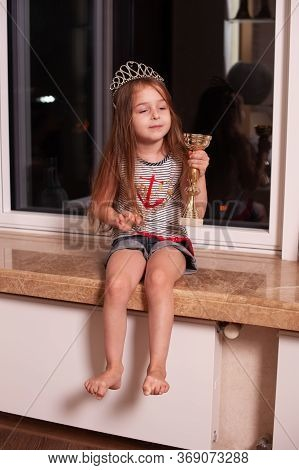 Cute Little Girl Sitting On Windowsill. Girl 5 Years Old With A Crown On Her Head. Child At Home On