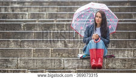 Girl Sits Waiting On Stone Stairs, Wearing Red Rain Boots And A Umbrella With Hearts Protecting Her