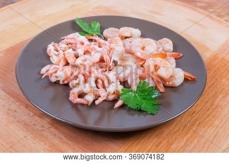 Cooked Peeled Tails Of King Prawns And Usual Shrimps On The Brown Dish On The Wooden Surface