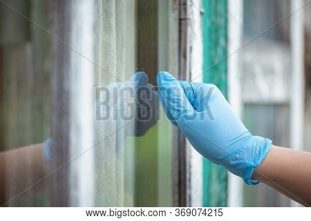 A Neighbor In The Medical Glove Knocks On The Window.
