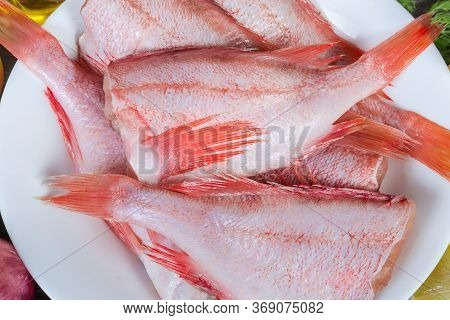 Uncooked Headless Gutted Carcasses Of Redfish Also Known As Ocean Perch On The White Dish, Top View
