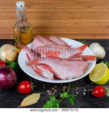 Raw Headless Gutted Carcasses Of Redfish Also Known As Ocean Perch On Dish Among The Spices, Fresh V