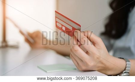 Close Up Woman Using Credit Card For Purchasing And Shopping Online On Mobile Phone