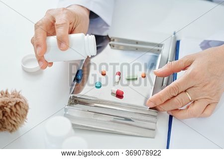 General Practitioner Putting Pills And Tablets In Stainless Steel Tray For Easy Sorting And Counting