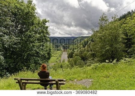 Young Caucasian Woman On A Bench On The Top Of A Mountain Overlooking River Valley With Green Trees