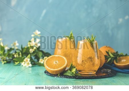 Two Glasses Of Orange Ice Drink With Fresh Mint On Wooden Turquoise Table Surface. Fresh Cocktail Dr