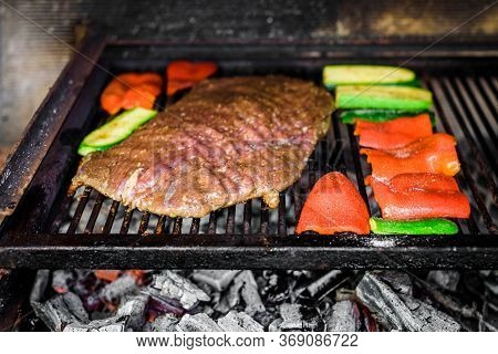 Grilling Marinated Angus Beef Flank Steak On Hot Coals Barbecue Grill.