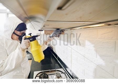 Cleaning Service Worker Spraying Detergent On Greasy Range Hood Filter In Kitchen Of Client