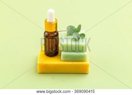 Soap Green And Yellow Color With Eucalyptus And Serum On Green Backgriund. Skin Care. Minimalism