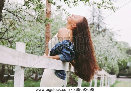 Portrait Young Carefree Hippie Girl In Denim Jacket With Long Brunette Hair On Countryside Garden Am