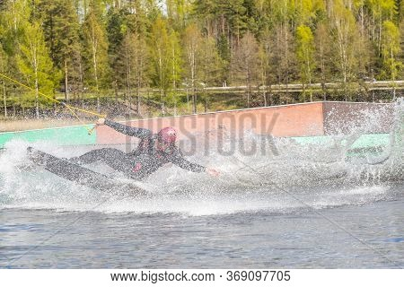 Fagersta, Sweden - Maj 26, 2020: Teen Wakeboarder On Wakeboard Landed In Water Surrounded By Spray.