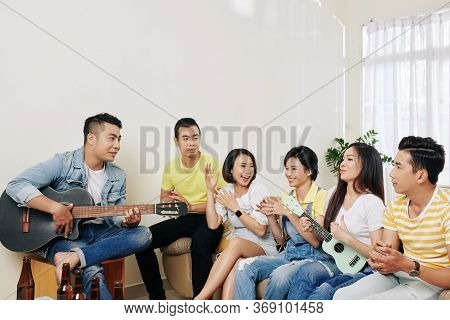 Cheerful Young Vietnamese People Paying Guitars And Singing At Home