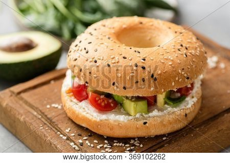 Bagel Sandwich With Cream Cheese, Avocado And Tomato On Wooden Serving Board, Closeup View. Sesame B
