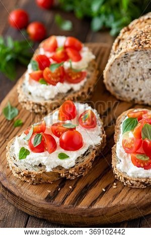 Bruschetta With Fresh Ricotta Cheese And Cherry Tomatoes On Wooden Board Decorated With Basil Leaves