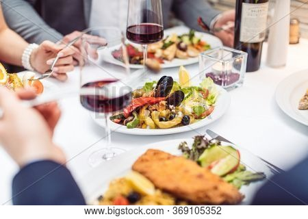 Close-up on Italian food on the table in restaurant with people eating and drinking