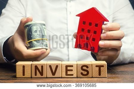 A Man With Dollars And A House Figurine And The Word Invest. Real Estate Financial Investment. Favor