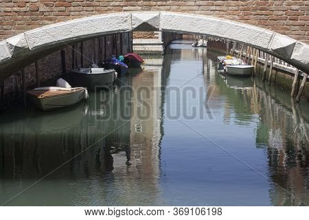 Venice, Italy - May 28 2016: Anchored Boats Under A Bridge In Venice In Arsenal Disctrict, Italy
