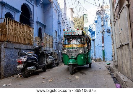 Jodhpur, India - December 9, 2019: A Tuk Tuk Driving Through An Alley With Traditional Blue Houses.