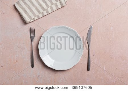Table Setting With Elegant White Empty Plate, Fork, Knife And Tablecloth. Silverware On Empty Plate