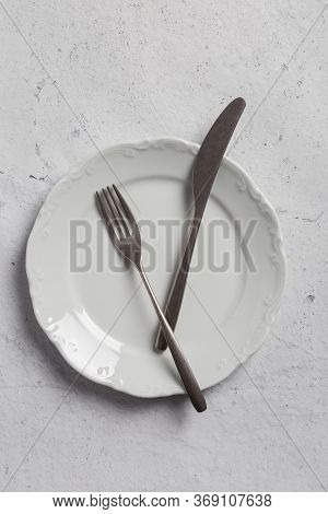Silverware On White Plate On Gray Concrete Background. Top View, Flat Lay, Concept Of Simple Table S