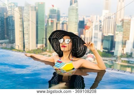 Young woman in a roof top swimming pool, infinity pool with beautiful city view. Vacation in Singapore.