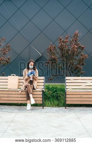 Young Woman Wearing A Protective Medicial Mask And Rubber Gloves, Sitting On A Wooden Bench And Usin