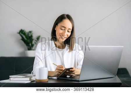 Woman Using Laptop At Workplace At Home Office And Writing Notes In Notepad. Frelance Work From Home