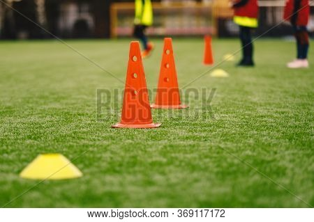 Sports Training Equipment On The Grass Pitch. Soccer Football Cones And Markers. Soccer Junior Playe