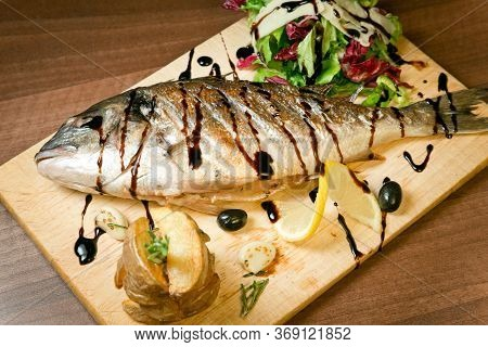 Grilled Sea Bass With Fried Potatoes And Fresh Salad . With Olives And Lemon On A Wooden Tray