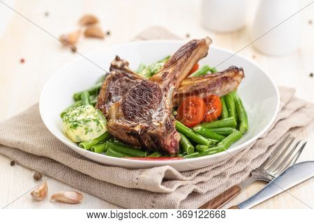 Grilled Lamb Chops With A Garnish Of Green Beans And Fragrant Butter. With Tomatoes And Fresh Thyme.