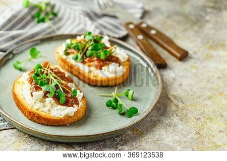 Canape Or Crostini With Toasted Baguette, Cottage Cheese, Fig Jam And Microgreen On Plate. Delicious