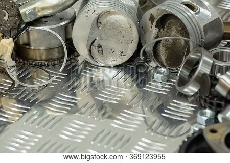 Old Car Spare Parts On Metal Workbench Background With Copy Space.