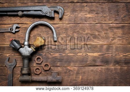 Old Rusty Water Tap And Wrench On Brown Wooden Workbench Background.
