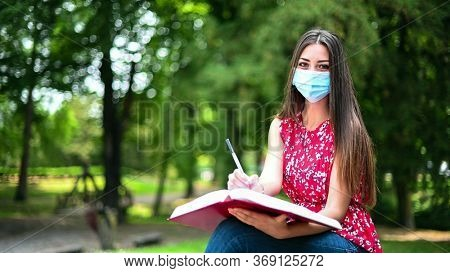 Beautiful female college student reading a book on a bench in a park and wearing a mask in coronavirus times