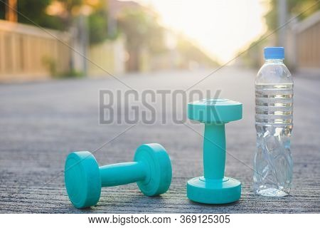Dumbbell Weights And Bottle On Street Blurred Background.metaphor Fitness And Workout Concept Exerci