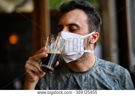 Young man trying to drink a beer wearing a mask, funny coronavirus concept