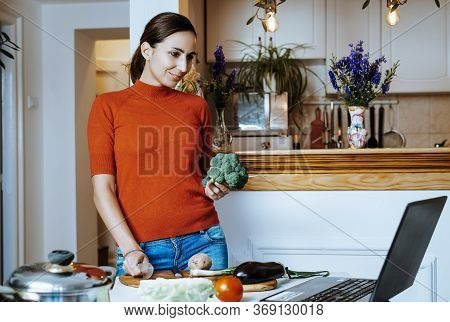 Woman Cooking Food In Kitchen. Young Woman Cooking Food In Kitchen Using Tablet Computer To Learn. D
