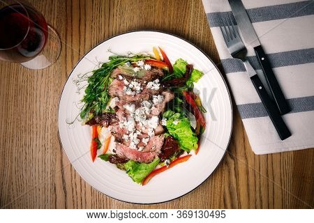 Delicious Salad With Roasted Meat And Vegetables Served On Wooden Table, Flat Lay. Food Photography