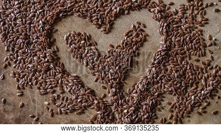 Flax Seeds Scattered On The Table In The Form Of A Heart. Super Food