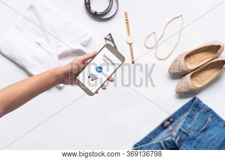 Female Hands Holding Phone With Online Shopping On The Screen