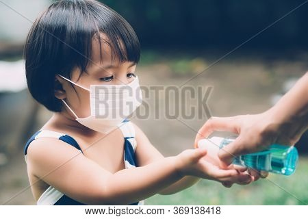 Mother Take Care Son With Face Mask And Sanitizer For Protection Disease Flu Or Covid-19 Outdoors, M