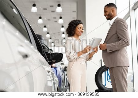 Car Sales. Automobile Seller Woman Showing Auto To African Businessman Standing In Dealership Showro
