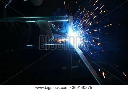 Sparks From Welding. A Man Will Weld Metal. Workplace Of The Welder. Garage Welder
